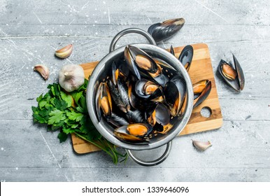 Fresh seafood clams with parsley and garlic. On a rustic background.