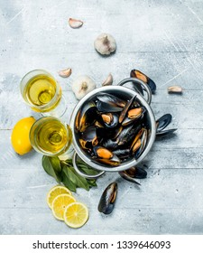 Fresh seafood clams with wine and lemon wedges. On a rustic background.