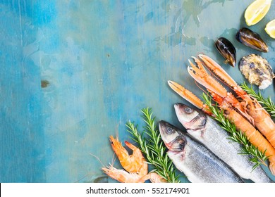 Fresh seafood and fish flat lay scene on blue background with copy space