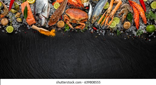 Fresh seafood, mussels, prawns, fish, crab, salmon steak, mackerel and other shells served on black stone