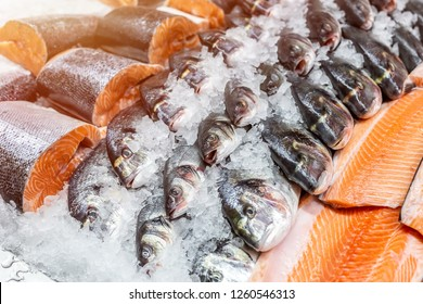 Fresh seafood on crushed ice at fish market. Raw dorado, seabass and salmon fillet on display counter at store. Fish filleting.