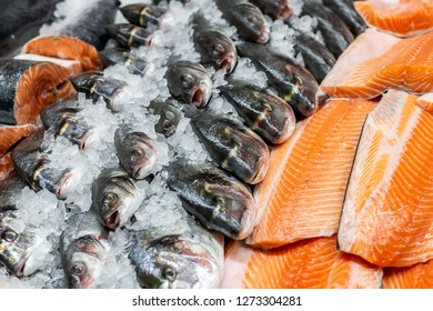 Fresh seafood on crushed ice at fish market. Raw dorado, seabass and salmon fillet on display counter at store. Fish filleting