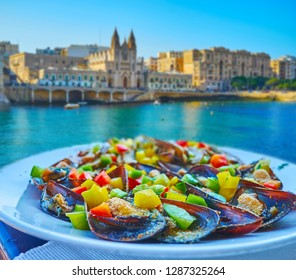 The fresh seafood is the perfect choice for lunch, restaurants at Balluta Bay offers fresh mussels with cheese, vegetables and fragrant herbs, with a view on Carmelite Church, St Julian's, Malta.
