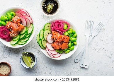 Fresh seafood recipe. Shrimp salmon poke bowl with fresh prawn, brown rice, cucumber, pickled sweet onion, radish, soy beans edamame portioned with black and white sesame. Food concept poke bowl.