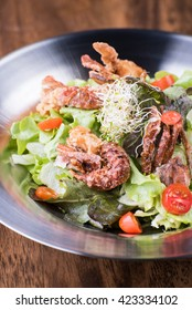 Fresh seafood salad with fried shrimps and fried crab on a stainless plate