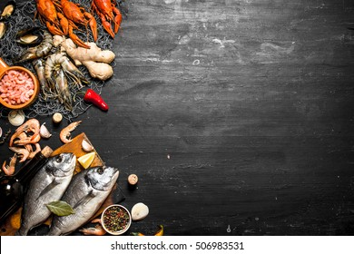 Fresh seafood. Two fresh fish with a bottle of wine. On a black chalkboard.
