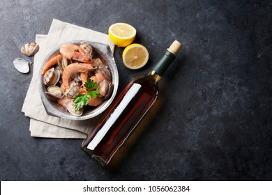Fresh seafood and white wine on stone table. Top view with copy space