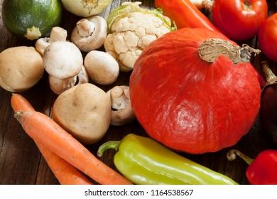 Fresh seasonal vegetables on wooden table. Pumpkin, carots, mushrooms, eggplant, tomato, zuccini, onions, garlic. Close up.