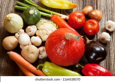 Fresh seasonal vegetables on wooden table. Pumpkin, carots, mushrooms, eggplant, tomato, zuccini, onions, garlic.
