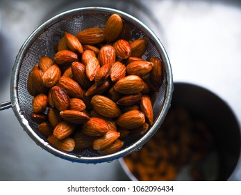 Fresh shelled almonds in a stainless steel colander or sieve ready to be used to ingredient in baking cooking or almond milk for drinking. close up high view, Healthy food. Nutrition food concept.