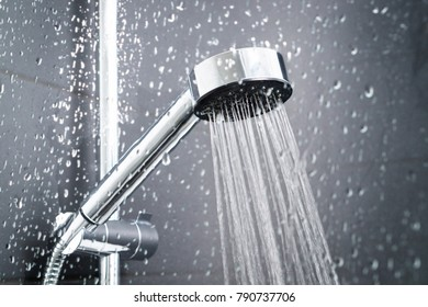 Fresh shower behind wet glass window with water drops splashing. Water running from shower head and faucet in modern bathroom.