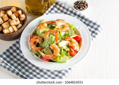Fresh shrimp salad made of tomato, ruccola, prawns, chicken breast, arugula, crackers and spices. Caesar salad in a white, transparent bowl on wooden background