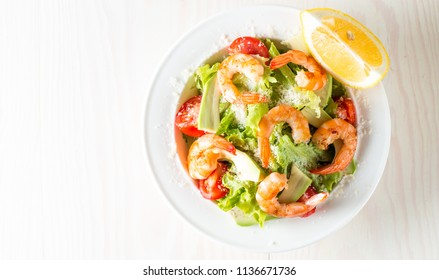 Fresh shrimp salad made of tomato, ruccola, avocado, prawns, chicken breast, arugula, crackers and spices. Caesar salad in a white, transparent bowl on wooden background. Seafood