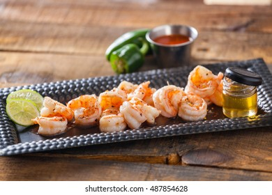 Fresh Shrimp Served On Black Plate On Wooden Table Cooked With Honey And Lime. Selective Focus.