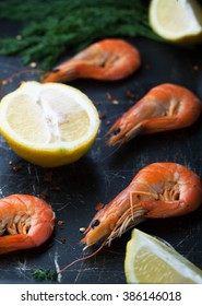 Fresh shrimp in the shell with a lemon, spices and herbs on a dark background