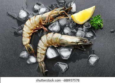 Fresh shrimps with lemon and ice on black background