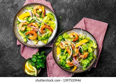Fresh Shrimps, Mango Avocado lettuce salad, olive oil and lemon dressing. healthy food. Top view, gray background.