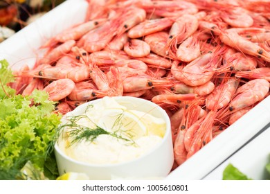 Fresh shrimps on the white plate with vegetable and dips. Bright day during outdoor wedding in Scandinavian style.