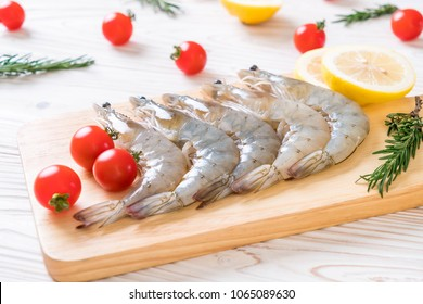 fresh shrimps or prawns raw on wooden board with ingredients