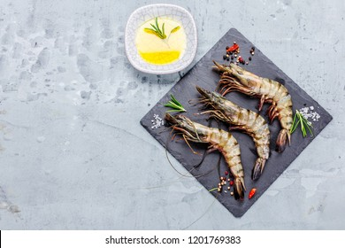 fresh shrimps or prawns raw on kitchen table board with ingredients