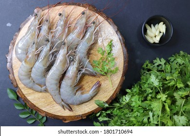 fresh shrimps or white prawns raw on wooden chopping board with coriander and curry leaves. on background with copy space.