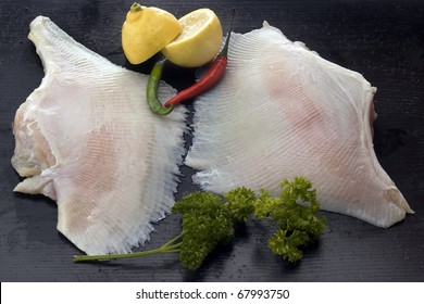 Fresh skate wings against black with condiments