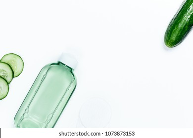 Fresh skin care tonic for face, cucumber slices and bottle with tonic, top view ingredients on white background