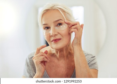 Fresh skin. Positive joyful woman applying eye patches on her face while wanting to have fresh skin