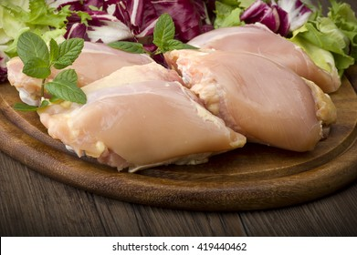 Fresh skinless chicken thighs and legs on cutting board