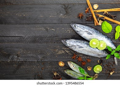 Fresh skipjack tuna fish on dark black wooden background, Fish with spices and vegetables, cooking background concept.