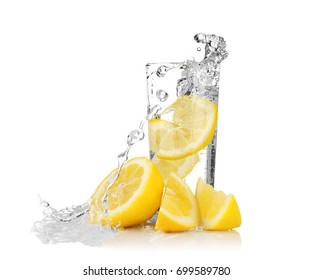 Fresh slice of lemon falling in glass with water on white background