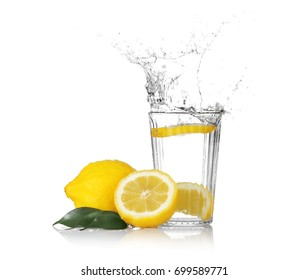 Fresh slice of lemon falling into glass with water on white background