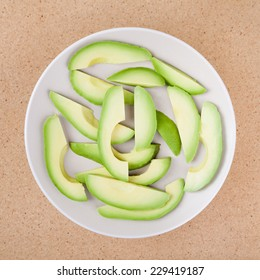 Fresh sliced avocado on plate, over wooden background.