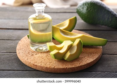 Fresh sliced avocados with an oil on a board, close up
