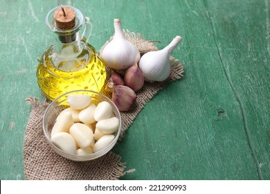 Fresh sliced garlic in glass bowl and oil in glass bottle, on wooden background