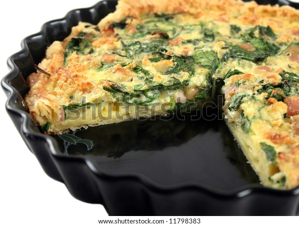 Fresh sliced homestyle spinach and bacon quiche straight from the oven.