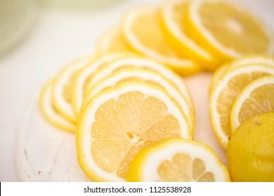 Fresh sliced lemon on a white wood cutting board.