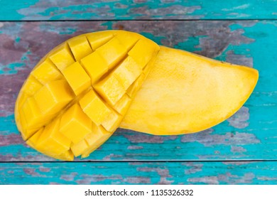 Fresh sliced mango fruit from above on wooden table.