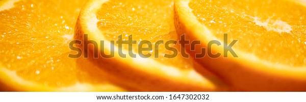 Fresh sliced oranges in a row. Macro, side view, copy space. Background of juicy oranges