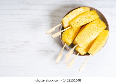Fresh sliced pineapple in bowl with copy space, top view
