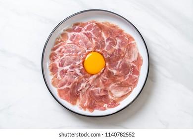 fresh sliced pork raw with egg for cooking or making shabu shabu and sukiyaki