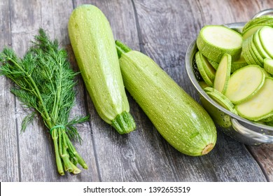 Fresh sliced raw bio zucchini and dill on wooden background. Cooking ingredient