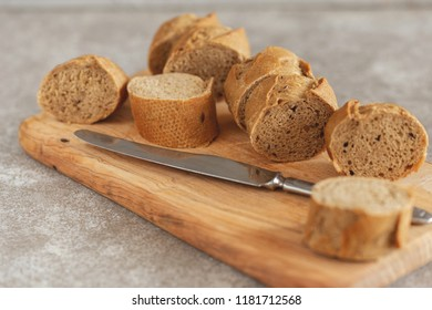 Fresh sliced rye baguette on the wooden cutting board. Horizontal view