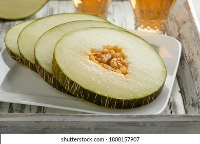 Fresh sliced sweet ripe Piel de Sapo melon on a dish close up