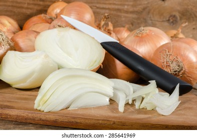 Fresh sliced and whole onions on wooden background