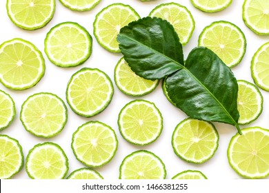 Fresh slices of bergamot fruits or kaffir lime and green leaf isolated on white background. Top view. Flat lay.