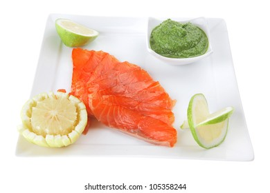 fresh smoked salmon on white plate with green sauce