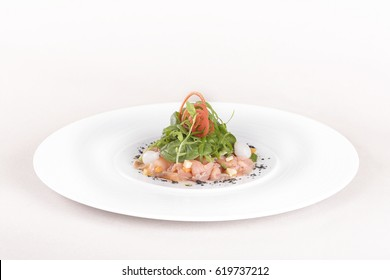 Fresh smoked salmon salad, served with rucola and baby spinach and pieces of vegetables, decorated with herbs, placed on white plate, light background, isolated