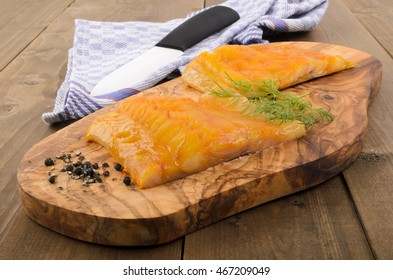 fresh smoked scottish haddock with dill on a wooden board