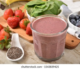 A fresh smoothie with organic strawberries, blueberries, raspberries, spinach, blackberries, banana and chia seeds